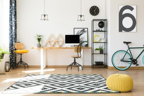 A pouf placed in a strategic position near a patterned rug in a living room