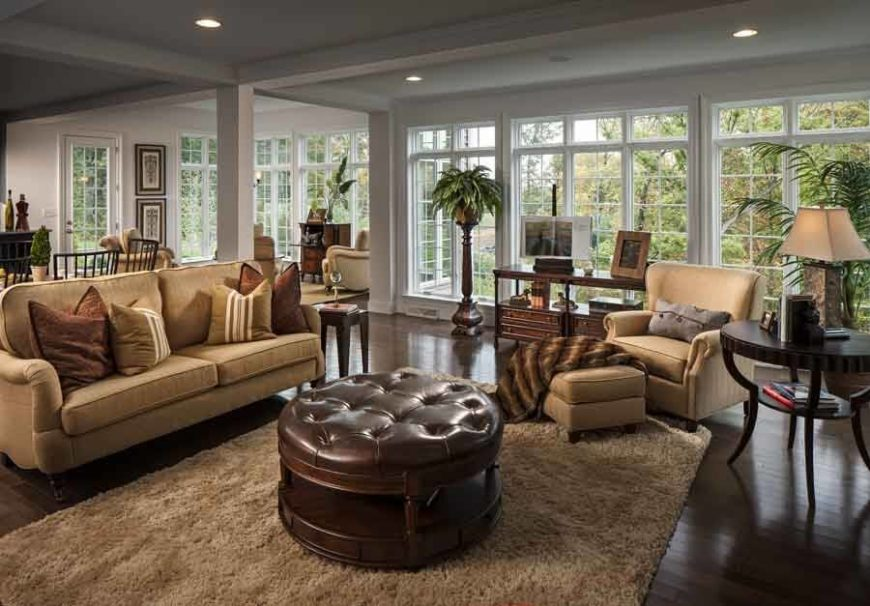 Round brown leather ottoman in the centre of a living room