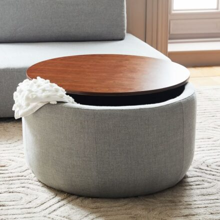 Grey round ottoman with shiny wooden top, with a white blanket peeping out